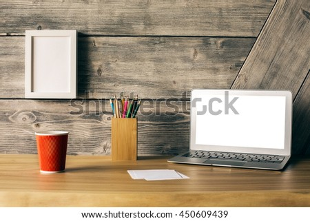Closeup of creative wooden designer desktop with blank white laptop screen, picture frame, take away coffee cup and stationery items. Mock up