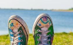closeup of custom painted shoe tops, modern footwear, beach in the background