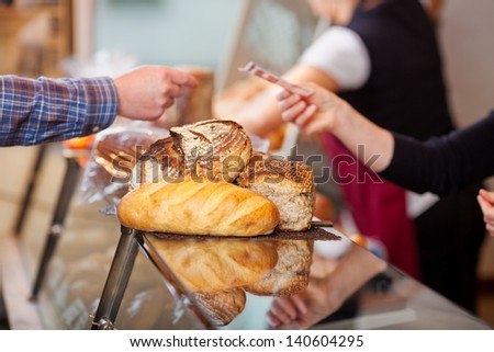 Closeup of customer paying for breads at bakery counter