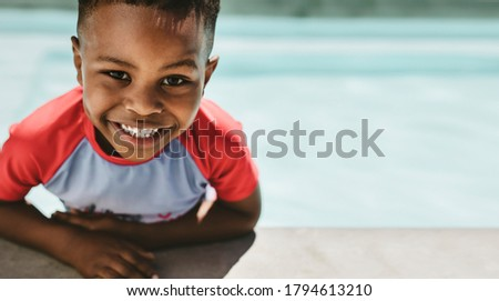 Closeup of cute boy on the edge of a swimming pool. Small boy in a pool looking at camera and smiling. Stock photo ©