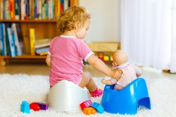 Closeup of cute little 12 months old toddler baby girl child sitting on potty. Kid playing with doll toy. Toilet training concept. Baby learning, development steps