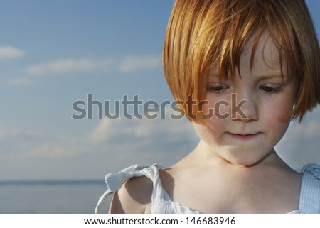 Closeup of cute little red haired girl looking down at beach