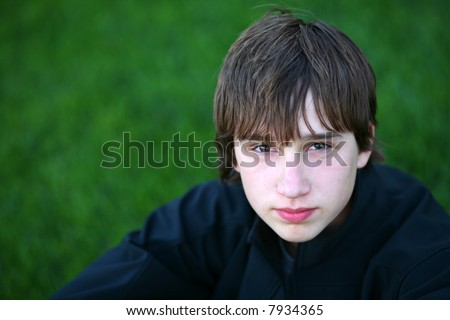 closeup of cute teen boy outside in grass