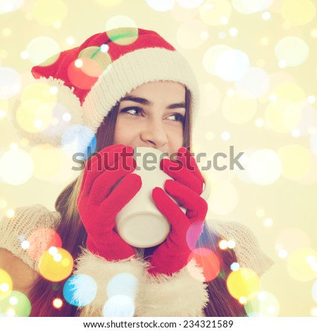 Closeup of cute young Christmas woman drinking tea. Teenage girl with Santa Claus hat and gloves drinking from big white mug. Square format. Colorful bokeh effect.