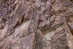 Closeup of dark dged shabby cliff cracks. Gray stone rock texture of mountains. Concept of geology and mountaineering