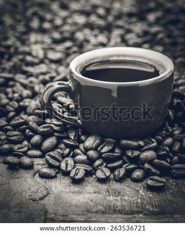 Closeup of dark roasted coffee beans and a cup filled with fresh hot coffee. Food and drink backdrop showing aromatic and beautiful coffee beans.