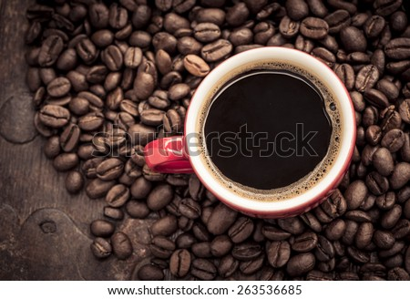 Closeup of dark roasted coffee beans and a red cup filled with fresh hot coffee. Food and drink backdrop showing aromatic and beautiful coffee beans.