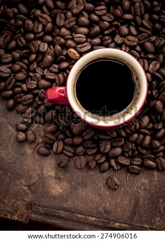 Closeup of dark roasted coffee beans and a red cup filled with fresh hot coffee. Food and drink backdrop showing aromatic and beautiful coffee beans. Can be used as a conceptual image for breakfast.