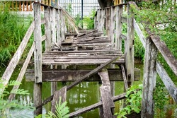 Closeup of  deformed and dilapidated wooden bridge over the canal , Damage wooden bridge decay concept.