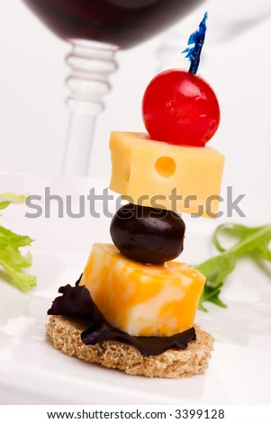 Closeup of delicious cheese and grape canape-sandwich made from cheese, black grapes and cherries served with salad and red wine in background