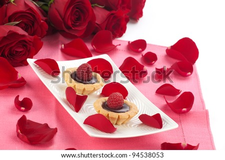 Closeup of delicious fresh raspberry chocolate petite cakes on Valentine day. Red roses and petals around.