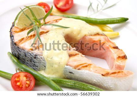 Closeup of delicious grilled salmon steak with tarragon sauce garnished with beans and cherry tomatoes.