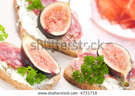 Closeup of delicious hard salami with figs canapes-sandwiches with soft cheese and parsley