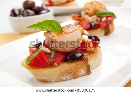 Closeup of delicious Olive - Tomato Bruschetta with garlic shrimp and pine nuts.
