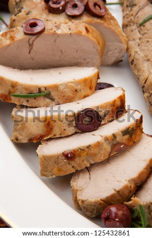 Closeup of delicious sliced roast pork tenderloin with olives, vermouth, and citrus.