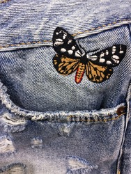 Closeup of denim embroidered flowers butterfly jeans texture with seams.