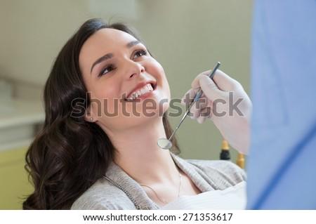 Closeup of dentist examining young woman\'s teeth