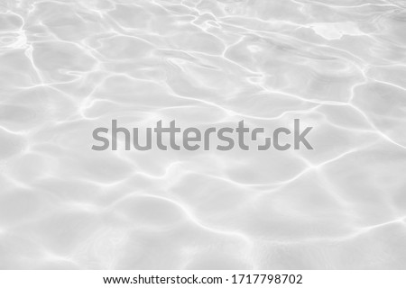Closeup of desaturated transparent clear calm water surface texture with splashes and bubbles. Trendy abstract nature background.