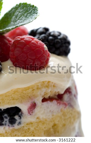 Closeup of dessert made of layers of cake filled with fresh fruits and mascarpone cream, topped with fresh raspberries and blackberries and a mint leave