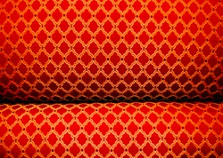 Closeup of Detailed Red, Gold and Black Ornate Upholstery Fabric and Cushion on Antique Chaise Longue