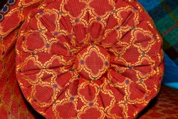 Closeup of Detailed Red, Gold and Black Ornate Upholstery Fabric and Cushions on Antique Chaise Longue
