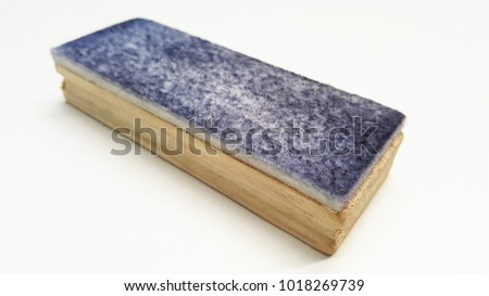 Closeup of dirty wooden whiteboard eraser or duster isolated on white background. Blue ink marker stains on whiteboards duster concept.