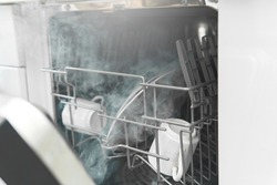 Closeup of dishwasher with a plates, cups and other dishware