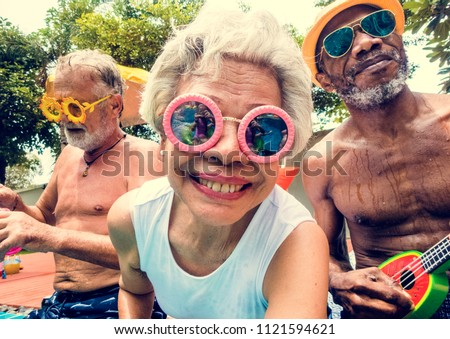 Closeup of diverse senior adults sitting by the pool enjoying summer together