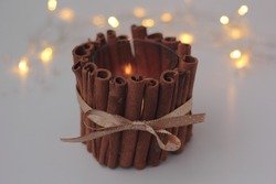 Closeup of DIY cinnamon candle holder with burning candle on white background. Concept of Christmas DIY and zero waste, sustainable decoration.