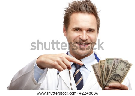 Closeup of doctor holding a  bundle of us dollar bills in his hand and points with other hand on it. Isolated on white.