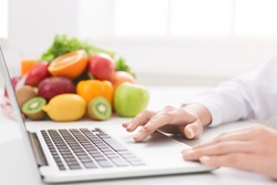 Closeup of doctor nutritionist typing on laptop at workplace with fresh fruits, empty space