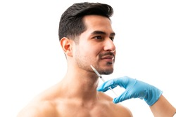 Closeup of doctor's hands giving botox injection into the skin of male model on white background