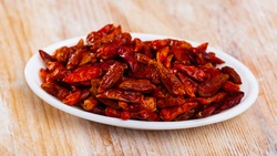 Closeup of dried pungent cayenne peppers in bowl on wooden table. Popular culinary spice