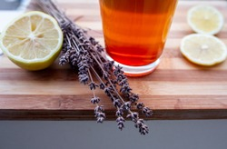 Closeup of drink next to lavender and lemon
