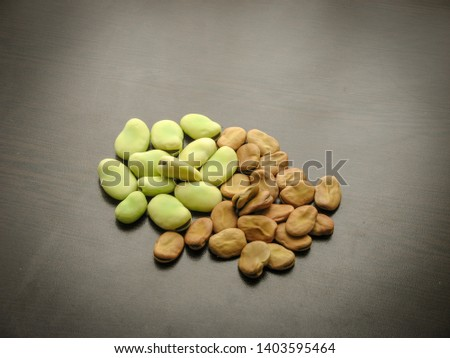 Closeup of dry and fresh broad beans seeds (Vicia faba) on wooden table. Dry and fresh broad beans on black background