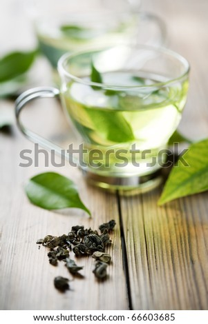 closeup of dry green tea, and a cup with fresh green tea. in the background, out of focus cup with fresh tea