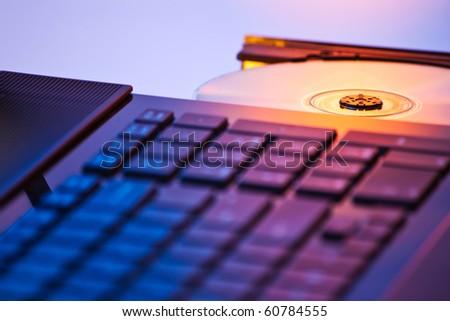 closeup of DVD-rom on laptop in warm light