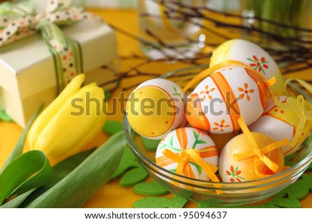 Closeup of easter eggs and yellow tulip on table. - stock photo