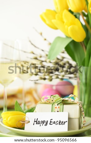 Closeup of easter gift and yellow tulip on table.