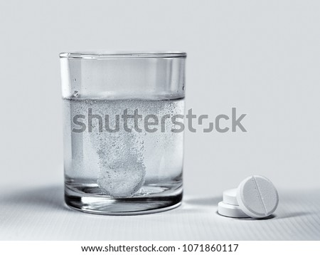 Closeup of effervescent tablets dissolving in a glass of water