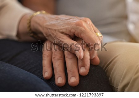 Closeup of elderly couple holding hands while sitting on couch. Husband and wife holding hands and comforting each other. Love and care concept.
