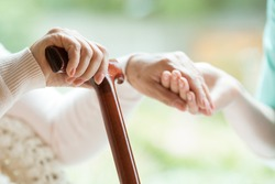 Closeup of elderly lady holding walking cane in one hand and holding volunteer's hand in the other
