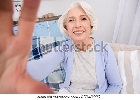 Closeup of elderly woman making self-photos, selfies on her mobile or smart phone while sitting on sofa or couch at home. Beautiful woman happy smiling and posing for camera.