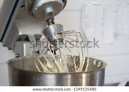 Closeup of electric mixer with whipped smooth dough for cake. Batter being whipped. Mixing white dough in bowl with motor mixer, baking cake