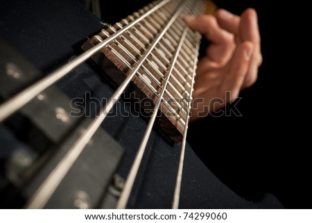 closeup of electrical bass guitar strings with fingers on it #74299060