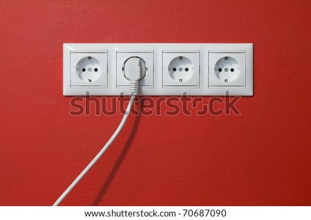Closeup of electrical outlets, cable and electric plug on red textured wall