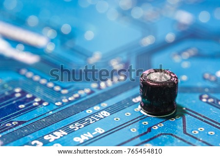 Closeup of electronic circuit board with capacitor blue