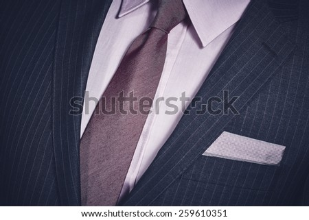 Closeup of elegant formal business suit with dark grey jacket with handkerchief in the pocket, shirt and necktie.