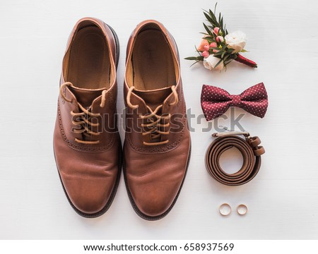 Closeup of elegant stylish brown male accessories isolated on white wooden background. Top view of bow-tie, belt, shoes, floral corsage, golden rings. Preparation for wedding concept. Horizontal photo