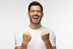 Closeup of emotional European man isolated on gray background showing white teeth while screaming with joy and victorious expression, holding hands in gesture of winner, looking happy